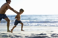 Father And Son Running Along Beach Together Wearing Swimming Costumes Stock Photo