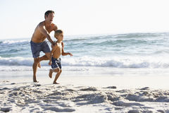 Father And Son Running Along Beach Together Wearing Swimming Costumes Stock Image