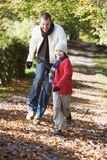 Father and son running along woodland path Royalty Free Stock Images