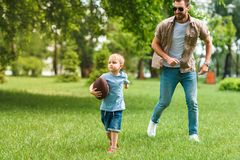 Father and son running with american football ball. At park royalty free stock image