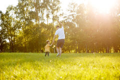 Father and son running away on meadow Stock Images