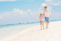 Father with son running barefoot on the sea surf Royalty Free Stock Images