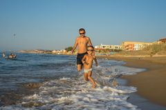 Father and Son 4-5 running on the Beach, Having Quality Family Time Together. USA. Sunset. Beautiful summer sunny day, blue sea. Picturesque landscape. - Image royalty free stock image