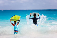 Father and son running with boogie boards Stock Image