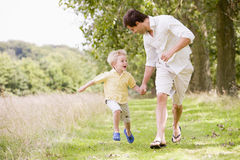 Father and son running on path holding hands Stock Photography