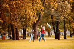 Father and son running while playing with a kite in an. Autumn park royalty free stock image
