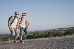 Father and son running on the road at the day time. Royalty Free Stock Photo