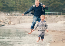 Father with son running on the sea surf line Stock Images
