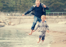 Father with son running on the sea surf line Royalty Free Stock Image