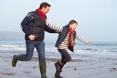 Father And Son Running On Winter Beach Stock Photos