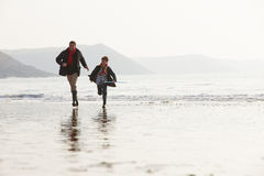 Father And Son Running On Winter Beach With Fishing Net royalty free stock photography