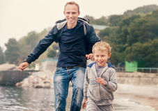 Father with son runs into the sea waves Royalty Free Stock Photography