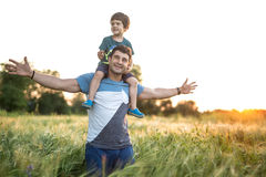 Father son in rye field. Son sits on the shoulders of his father on the sunset background. Man stands in the rye field with hands stretched to the sides. They stock photo