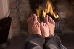 Father and son's Feet warming at a fireplace royalty free stock photography