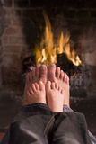 Father and son's feet warming at a fireplace Royalty Free Stock Photos