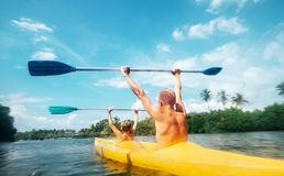 Father and son are sailing in the canoe in lagoon in sunny day Royalty Free Stock Photography
