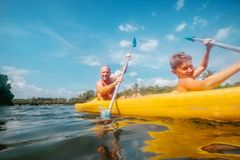 Father and son are sailing in the canoe in tropical lagoon Stock Images