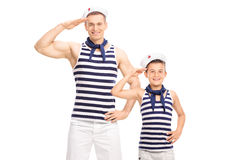Father and son in sailor uniforms smiling and saluting. Towards the camera isolated on white background Stock Images