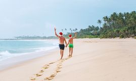 Father and son in Santa hats walk on the sand tropical beach. Ou Royalty Free Stock Photos