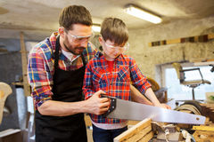Father and son with saw working at workshop Royalty Free Stock Photos