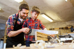 Father and son with saw working at workshop. Family, carpentry, woodwork and people concept - father and little son with saw sawing wood plank at workshop Royalty Free Stock Images