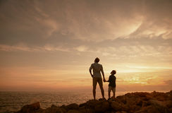 Father with son on the sea coast in sunset time Royalty Free Stock Images