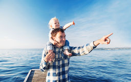 Father and son on sea and sky backgrounds. Little boy is sitting on father`s shoulders and points forward. Parent and child together at summer. Family Royalty Free Stock Photography