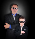 Father and Son Secret Agents with Sunglasses. A father and son are wearing business suits with sunglasses pretending to be secret agents or bodyguards on a black royalty free stock photography