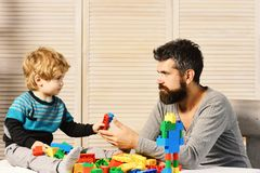 Father and son with serious faces play with toy bricks. Father and son with serious faces look at each other and play with toy bricks. Family and childhood Stock Images
