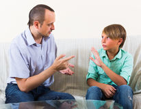 Father and son seriously talking at home Royalty Free Stock Photos