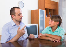 Father and son seriously talking at home Stock Image