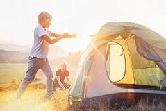 Father and son setting camping tent on the sunset mountain valley royalty free stock image