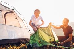 Father and son setting tent on sunset forest glade royalty free stock image
