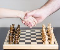 Father and son shaking hands before the game of chess.  Stock Photography