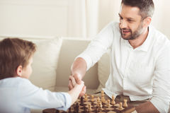 Father and son shaking hands after playing chess board game. At home royalty free stock image