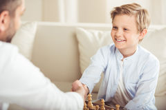 Father and son shaking hands after playing chess board game. At home royalty free stock photos