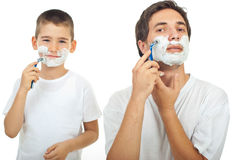Father and son shaving. Father shaving in the mirror and the son imitate father in background Royalty Free Stock Photography