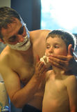 Father and Son Shaving in Bathroom. A father is teaching his son how to shave and wiping shaving cream on his face in the bathroom Stock Photos
