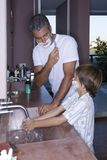 Father and son shaving in the bathroom. Son copying father shaving in the bathroom Stock Photo