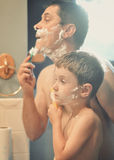 Father and Son Shaving in the Bathroom. A father is teaching his son how to shave and wiping shaving cream on his face in the bathroom Stock Photos