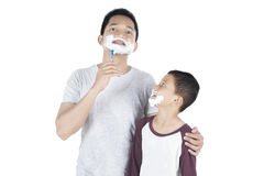 Father and son shaving beard on studio Royalty Free Stock Photo