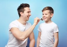 Father and son shaving. On light background Stock Photos