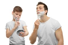 Father and son shaving. On white background Royalty Free Stock Photo