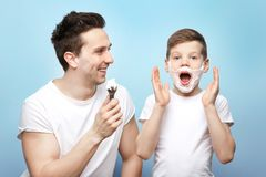 Father and son shaving. On light background Stock Image