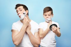 Father and son shaving. On light background Royalty Free Stock Image