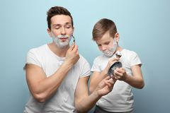 Father and son shaving. On light background Royalty Free Stock Photography
