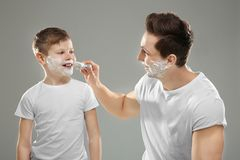Father and son shaving. On light background Stock Photography