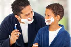 Father son shaving. Playful father and son shaving together at home bathroom royalty free stock photos