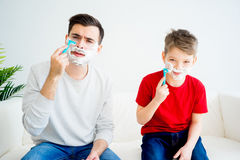 Father and son shaving. Father teaching his son to shave and having fun together Stock Photography