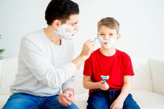 Father and son shaving. Father teaching his son to shave and having fun together Stock Images